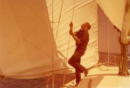 A photograph shows Gerald Hartwig hoisting a sailboat's sail.