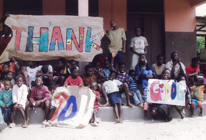 Children and staff of the New Life Orphanage pose for a photo and hold thank you signs.