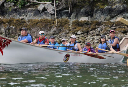 People wearing lifejackets paddle through the water in a large canoe.