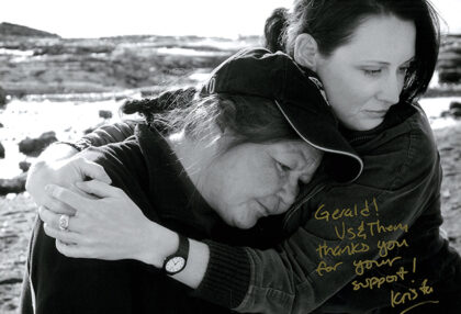 A black-and-white shot from the documentary Us and Them. A woman holds another in an embrace.